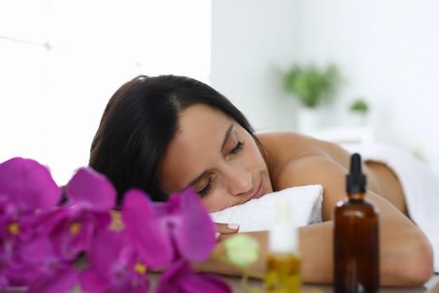 Mulher com os olhos fechados encontra-se na mesa de massagem no salão spa. conceito de relaxamento e relaxamento após um dia de trabalho