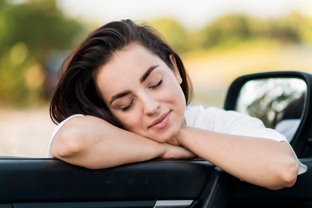 Mulher com os olhos fechados encostada na porta de um carro