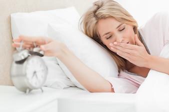 Mulher com os olhos fechados está chegando para silenciar seu despertador