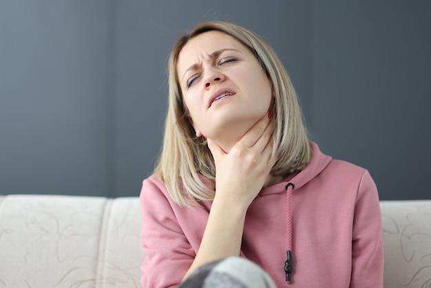 Mulher com os olhos fechados leva a mão à garganta. conceito de doenças e sintomas da garganta