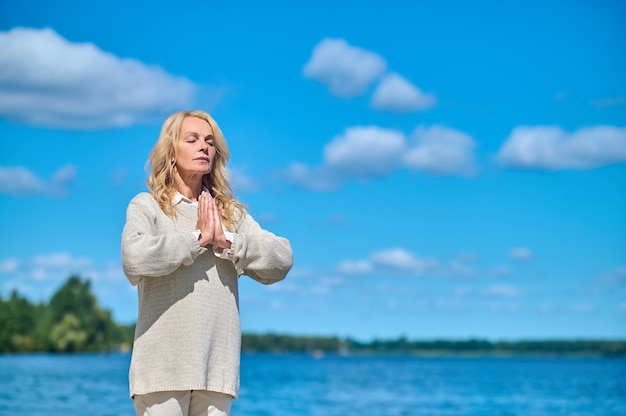 Mulher com os olhos fechados meditando na natureza