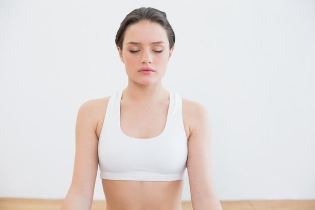 Mulher com os olhos fechados no estúdio de ginástica