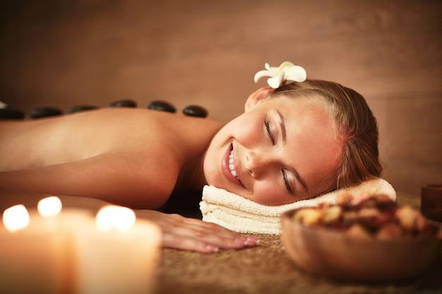 Mulher com os olhos fechados recebendo a massagem com pedras quentes