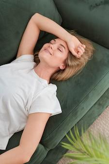 Mulher com os olhos fechados relaxando no sofá