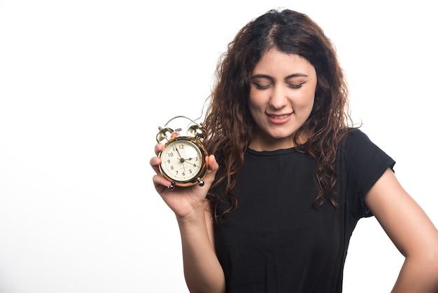 Mulher com os olhos fechados, segurando o relógio no fundo branco. foto de alta qualidade