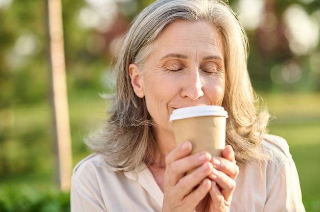 Mulher com os olhos fechados segurando um copo de café