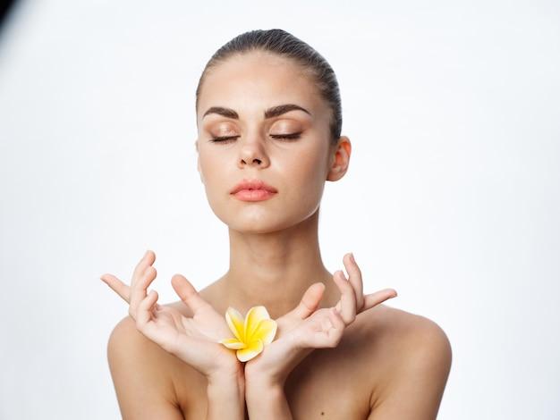 Mulher com os olhos fechados segurando uma flor amarela com as mãos limpas a pele