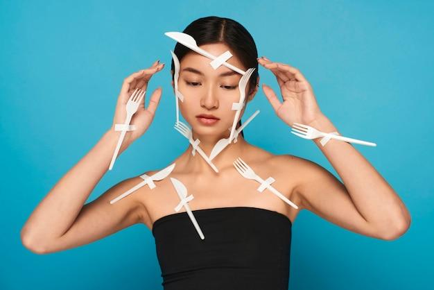 Mulher com os olhos fechados sendo coberta com talheres de plástico branco