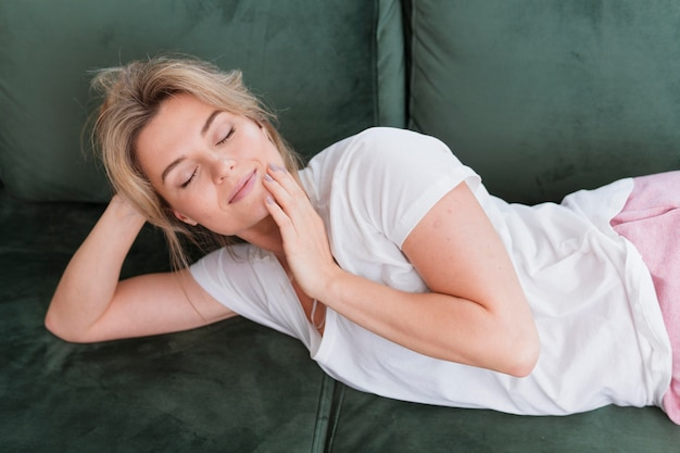 Mulher com os olhos fechados, sentado no sofá