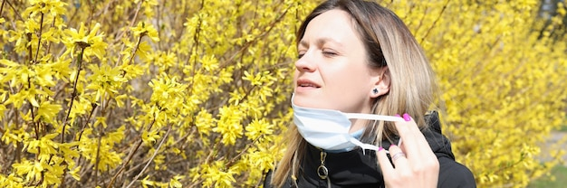 Mulher com os olhos fechados tirando a máscara protetora do rosto perto de uma árvore em flor