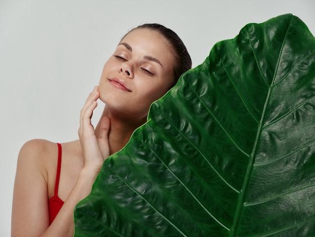 Mulher com os olhos fechados tocando o rosto com a mão e folha verde palmeira pele clara aparência natural