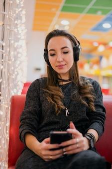 Mulher com os olhos fechados, usando fones de ouvido, olhando para o telefone perto de luzes de natal