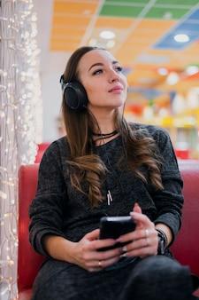 Mulher com os olhos fechados, usando fones de ouvido, segurando o telefone perto de luzes de natal