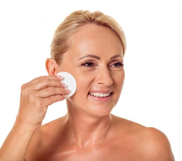 Mulher com os ombros desencapados que limpam a face usando o disco do algodão.
