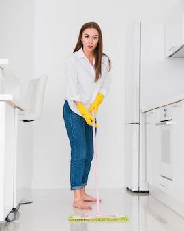 Mulher com os pés descalços, limpando a cozinha