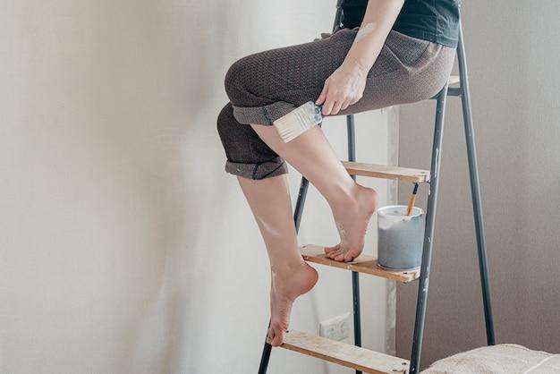 Mulher com os pés descalços manchados com tinta branca sentada no topo de uma escada segurando um pincel na mão