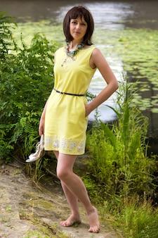 Mulher com os pés descalços na margem de um lago