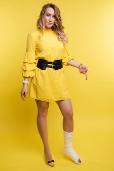 Mulher com osso quebrado em fundo amarelo.