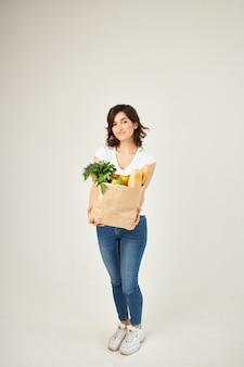 Mulher com pacote de comida saudável supermercados entrega luz de fundo