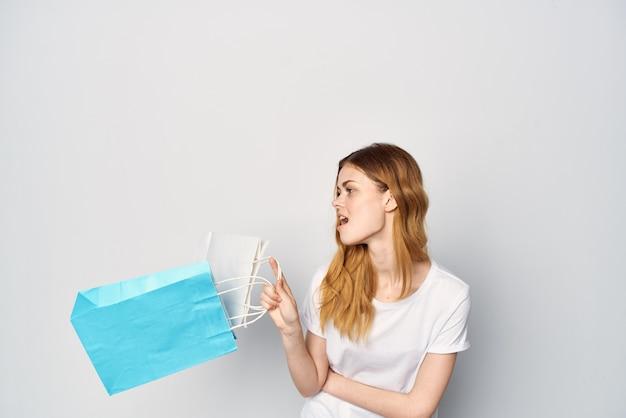 Mulher com pacotes na loja de mãos e divertida shopaholic