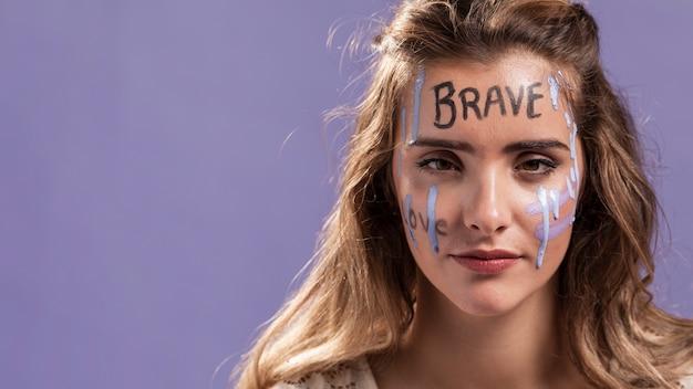 Mulher com palavras pintadas no rosto e cópia espaço