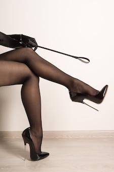 Mulher com palmada em couro preto brilhante com salto agulha e salto agulha no tornozelo