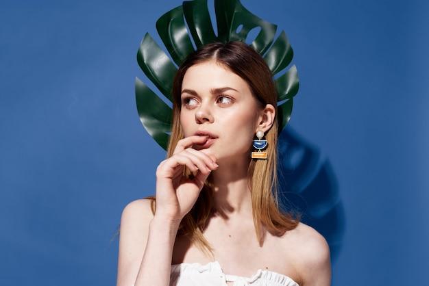 Mulher com palmeiras folha verde viajar parede exótica azul.