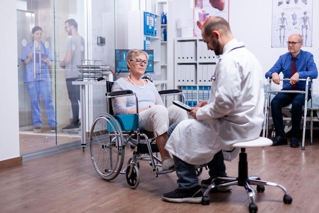 Mulher com parkinson sentada em uma cadeira de rodas em um quarto de hospital durante o exame médico