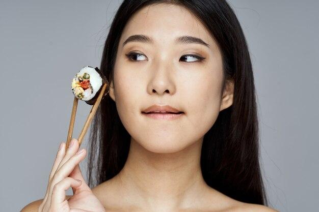 Mulher com pauzinhos de madeira rolos de sushi modelo de aparência asiática
