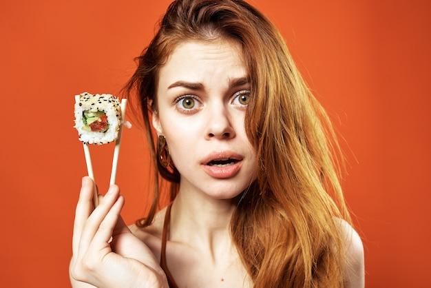 Mulher com pauzinhos de sushi rola comida japonesa lanche