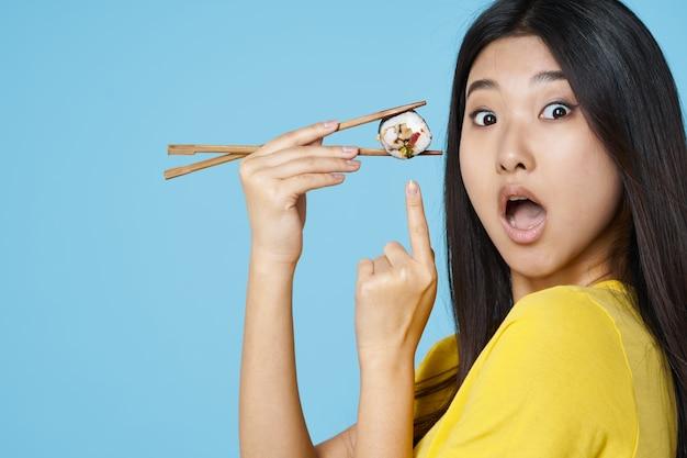 Mulher com pauzinhos sushi rola frutos do mar aparência asiática comida dieta