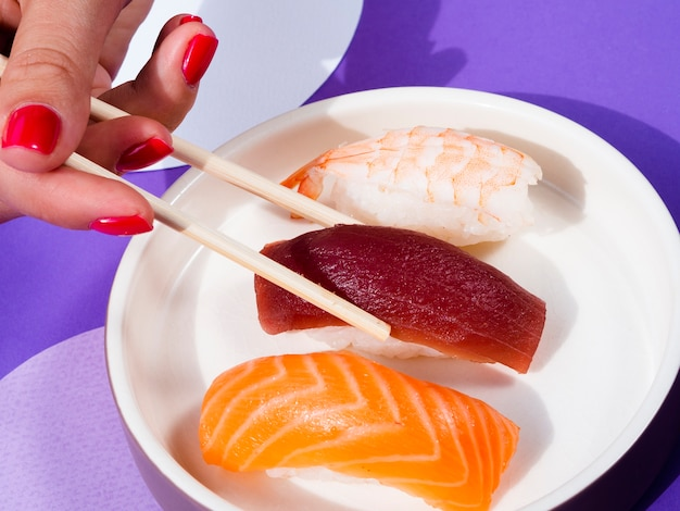 Mulher com pauzinhos tomando uma placa de forma de sushi de atum