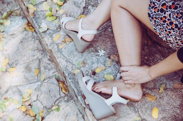 Mulher com pé ferido e sofrendo de dor nas pernas ao ar livre por causa de sapato desconfortável