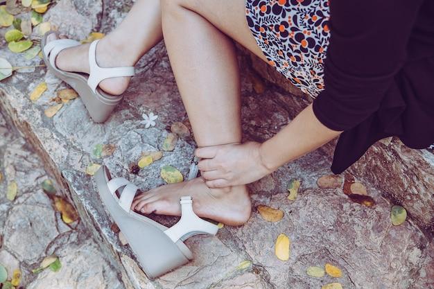 Mulher com pé machucado e sofrendo de dores nas pernas ao ar livre por causa de sapatos desconfortáveis, entorse de tornozelo com salto alto branco.