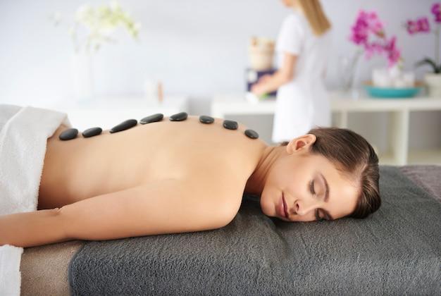 Mulher com pedras de massagem nas costas Foto gratuita