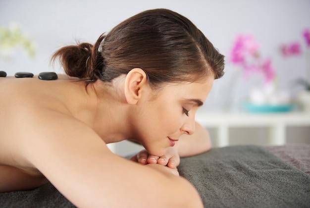 Mulher com pedras de massagem nas costas