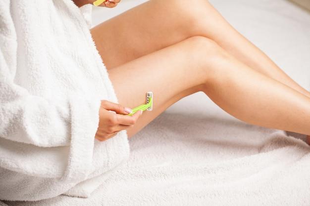 Mulher com pele bonita depila as pernas com uma navalha