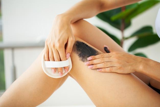 Mulher com pele bonita nos pés aplica creme anti-celulite na perna