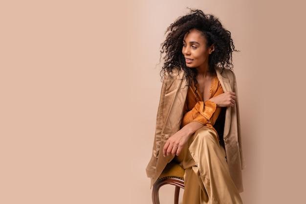 Mulher com pele bronzeada com cabelos cacheados perfeitos em elegante blusa laranja e calça de seda, sentada na parede bege de cadeira vintage.