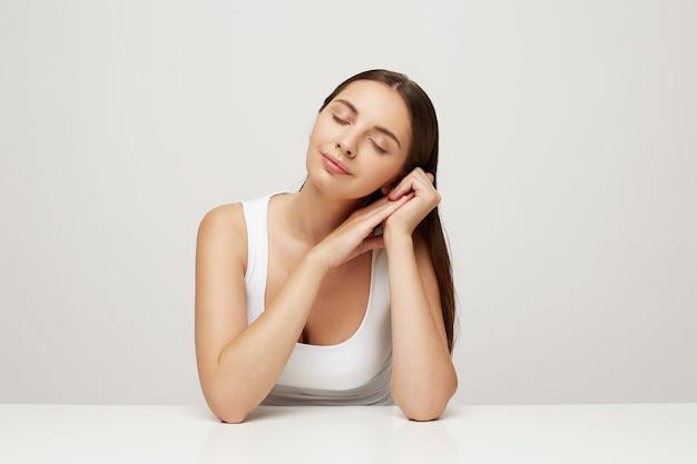 Mulher com pele fresca e saudável perfeita sentada à mesa, as mãos juntas perto do rosto e a cabeça deitada sobre elas