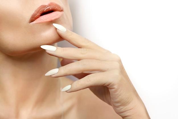 Mulher com pele limpa e saudável e uma longa manicure com esmalte de leite close-up.