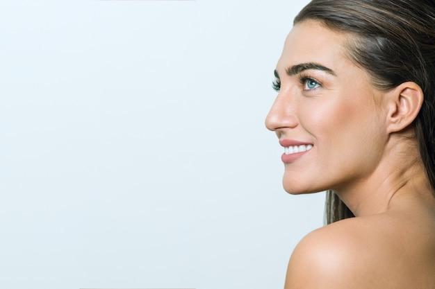 Mulher com pele limpa, maquiagem natural, cabelos lisos e saudáveis