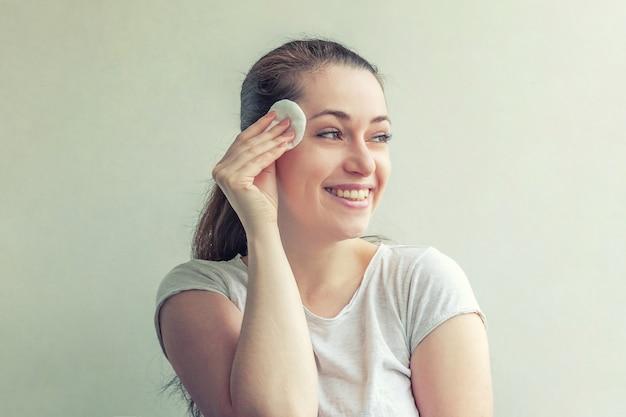 Mulher com pele macia e saudável removendo maquiagem com almofada de algodão isolada no fundo branco