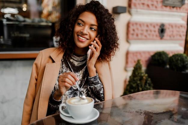 Mulher com pele negra e sorriso sincero, falando por telefone e curtindo