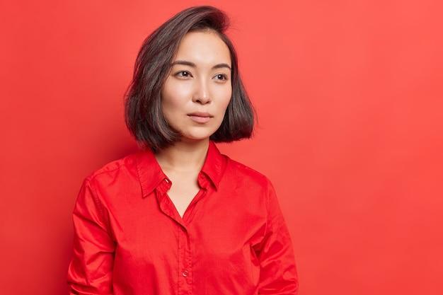 Mulher com pele saudável concentrou o olhar à distância, pensa na decisão, mergulhada em pensamentos, usa poses de camisa em vermelho brilhante