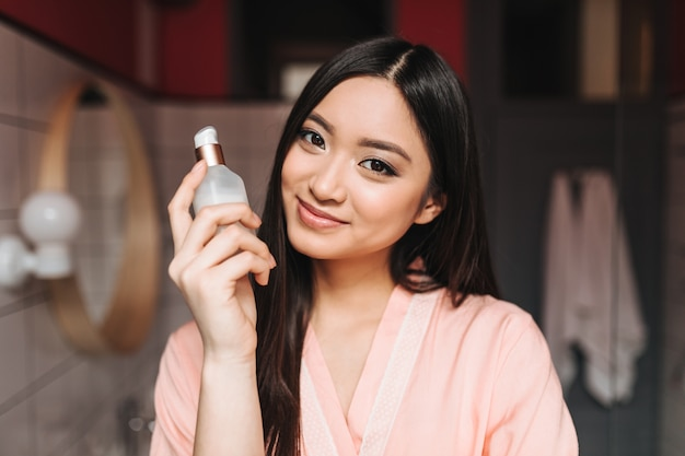 Mulher com pele saudável é fofa sorrindo e posando com creme facial na parede do banheiro