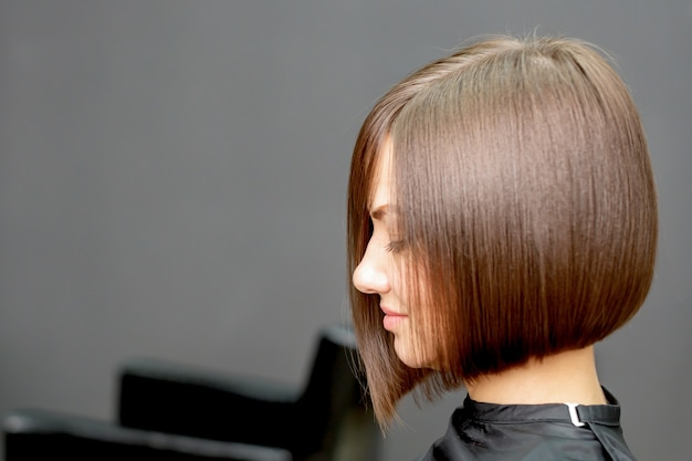 Mulher com penteado curto em salão de cabeleireiro com espaço de cópia.