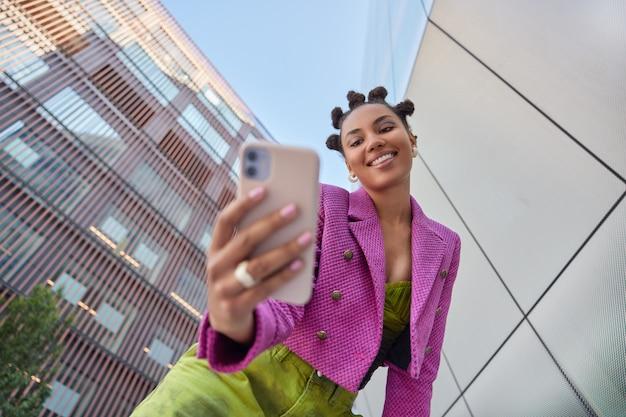 Mulher com penteado vestida com roupas da moda faz videochamada ou selfie via smartphone usa aplicativo móvel passeios em cenário urbano filmes vlog para redes sociais
