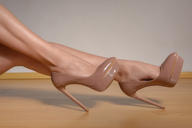Mulher com pernas bem torneadas e sapatos de salto alto laqueado marrom