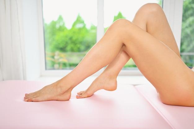 Mulher com pernas bronzeadas com pele macia suave perfeita